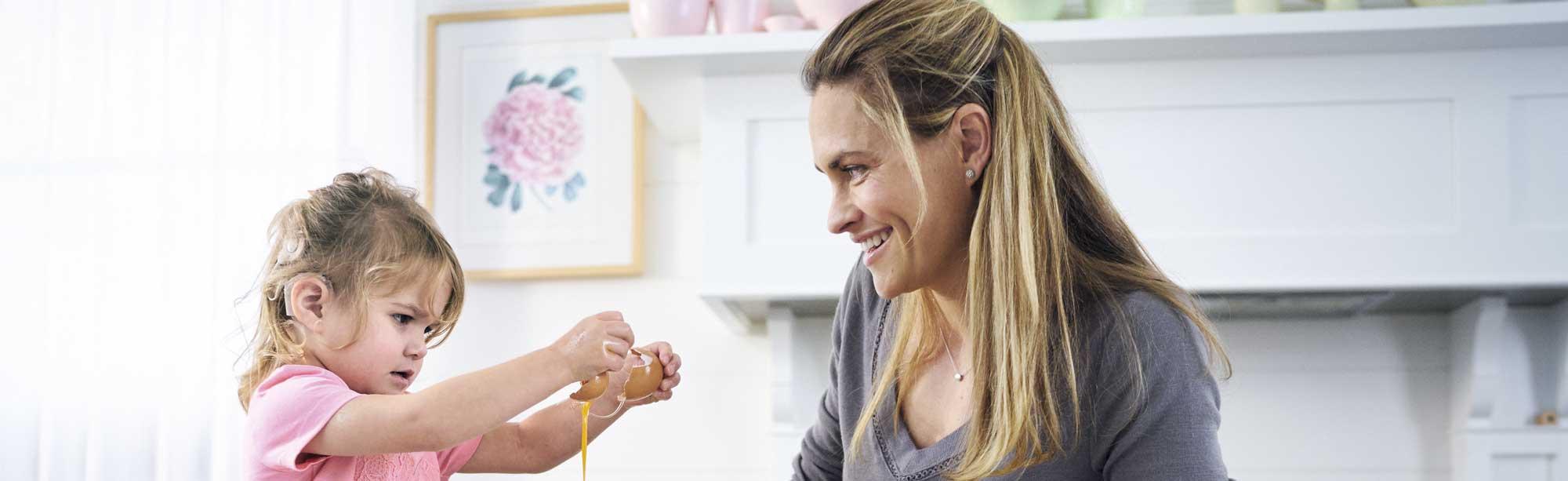 Niña con audífono GAES rompe un huevo mientras su madre la mira