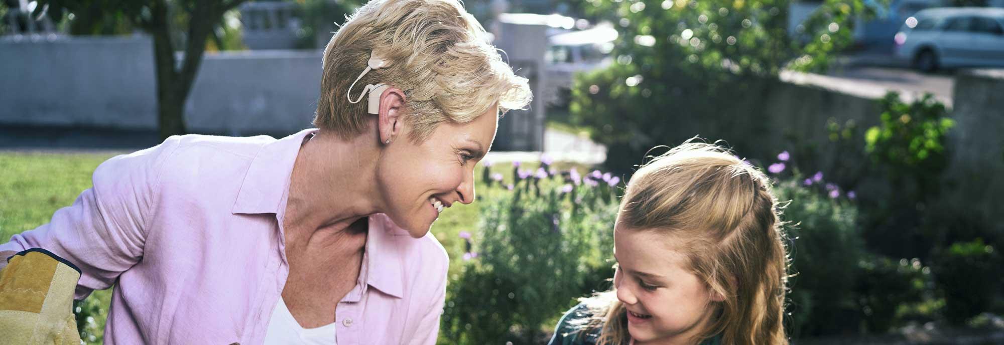 Mujer con audífono GAES hace jardinería con su hija